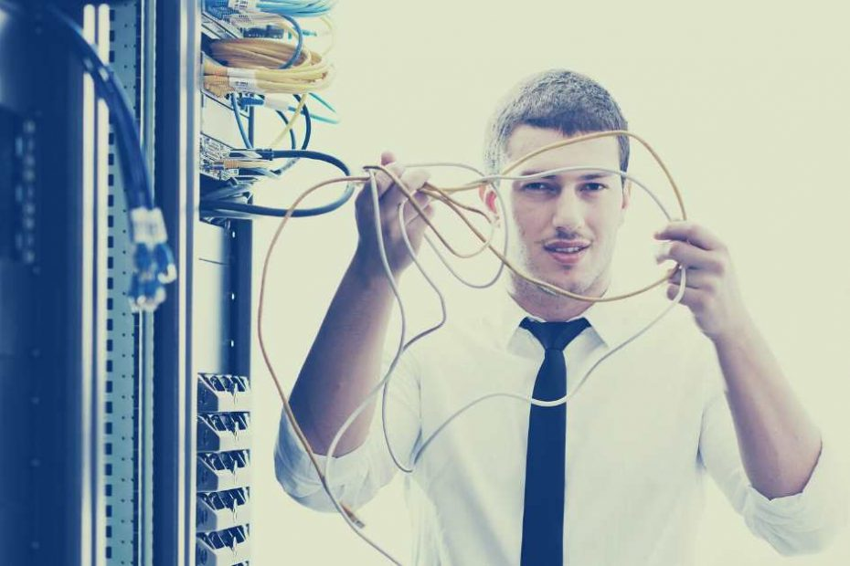 man holding cables next to server cabinet